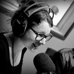 Black and white portrait photo of Dr. Rony Duncan, Senior Research Fellow, Murdoch Children's Research Institute. She is speaking into a microphone with a set of large headphones on her head. She is wearing glasses.